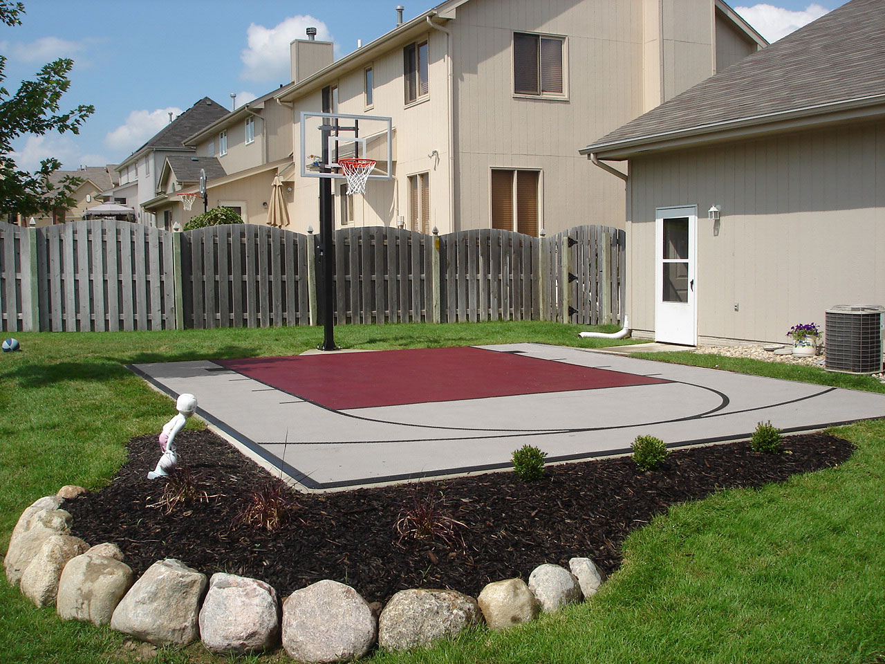 Gray and burgundy backyard basketball court