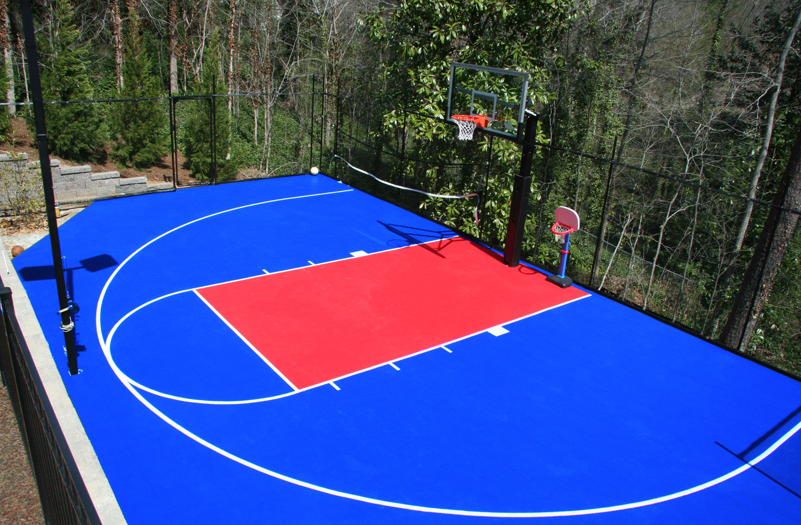 Backyard basketball half court in bright blue and red