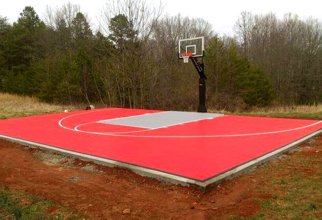 3/4 View of bright red basketball half court with gray key