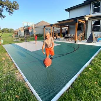 Boys playing basketball on evergreen and gray half court
