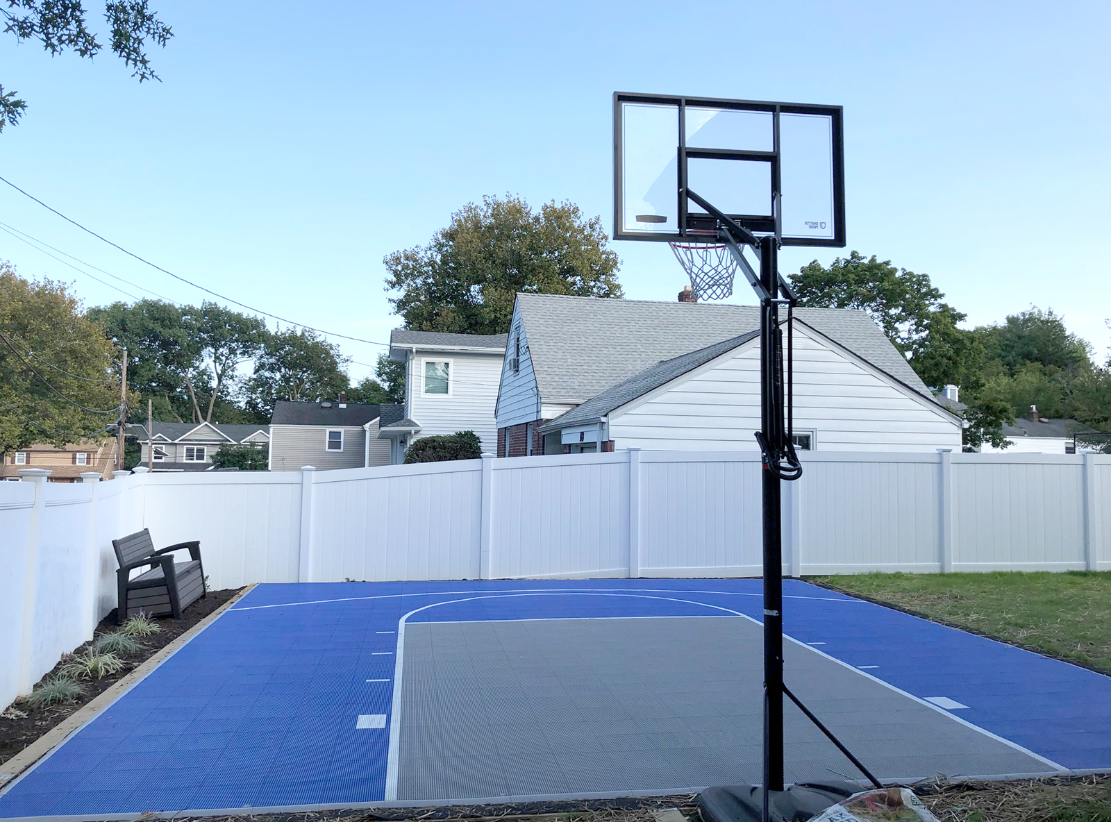 Bright blue and gray basketball half court in a fenced backyard