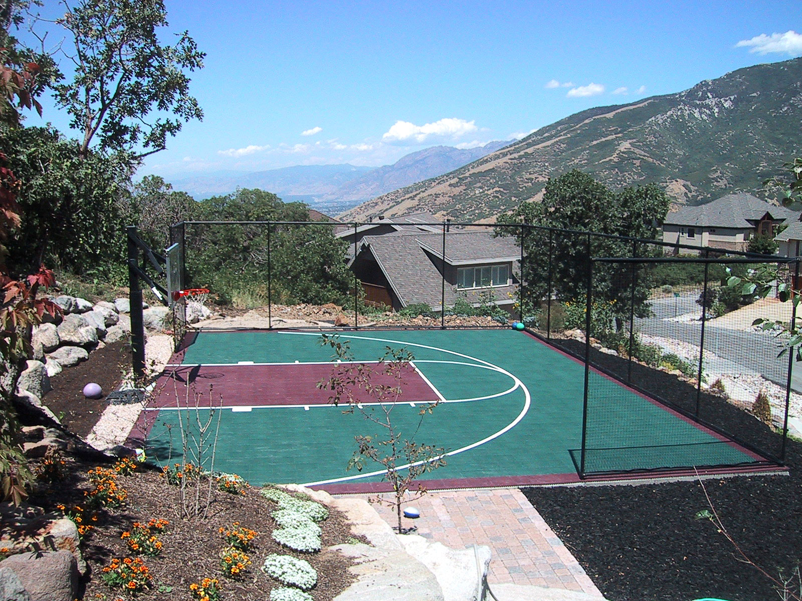 Fenced backyard basketball half court in burgundy and evergreen