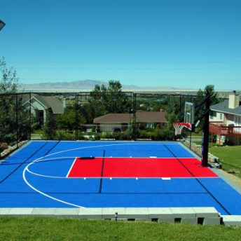 Multi-court in bright blue and red with lights and fencing