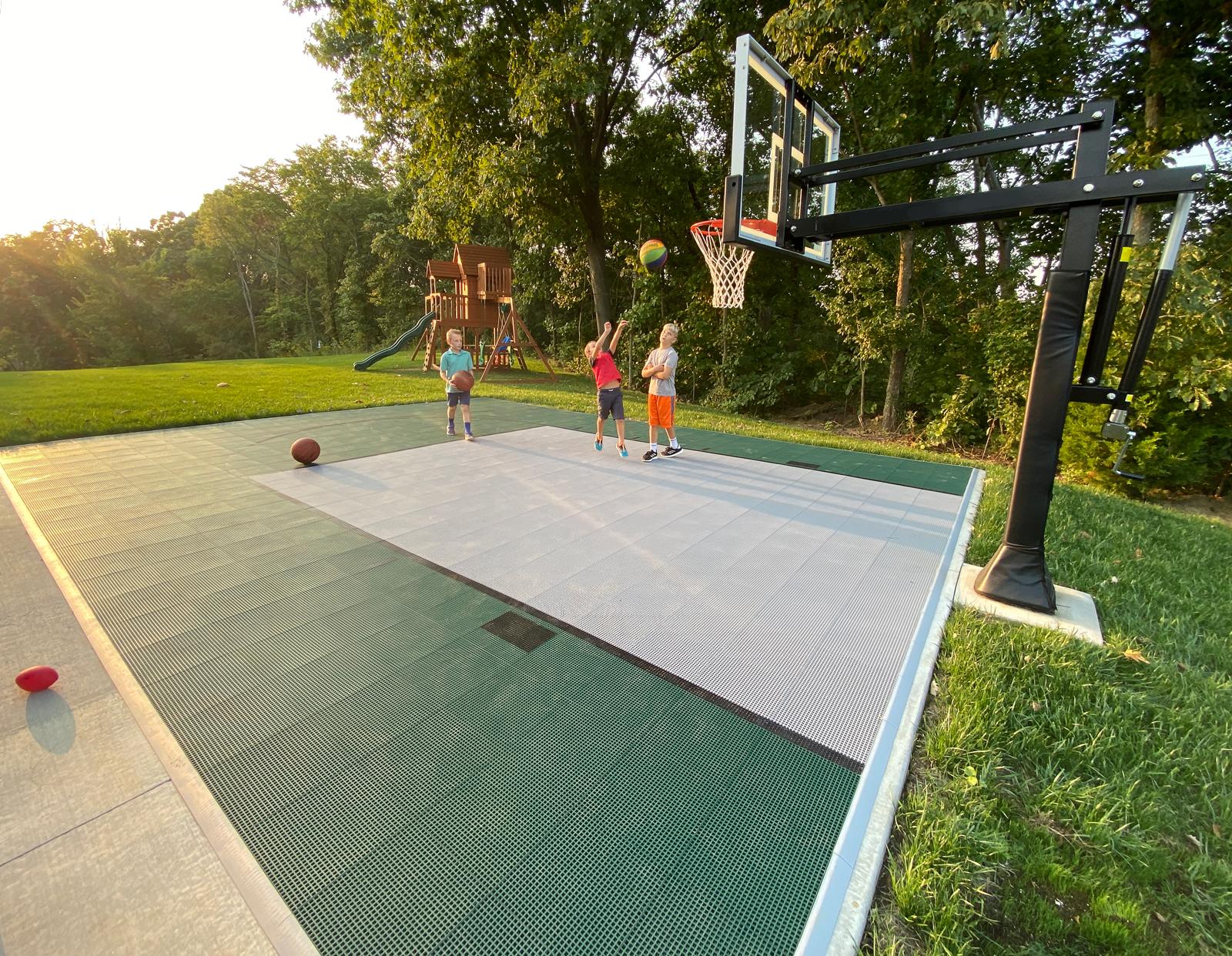Kids playing basketball on an Evergreen and Gray basketball half court